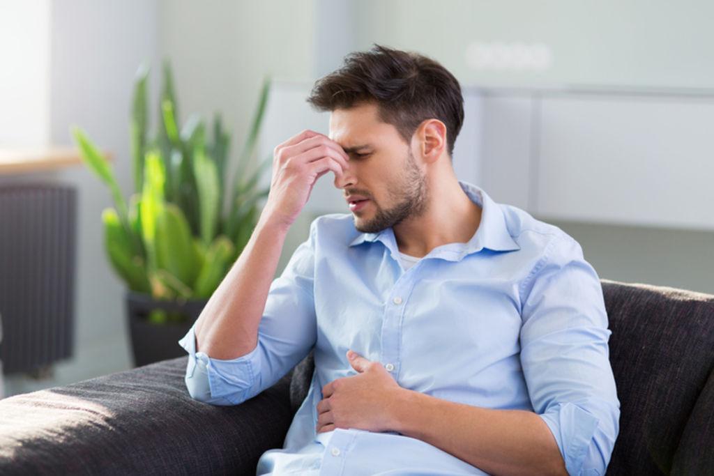Homem incomodado com a mão no rosto e no estômago | Principais causas da azia