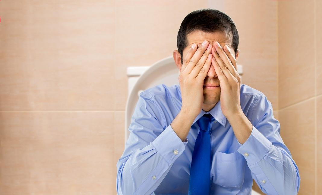 Homem preocupado sentado no vaso | O que é hemorroida?