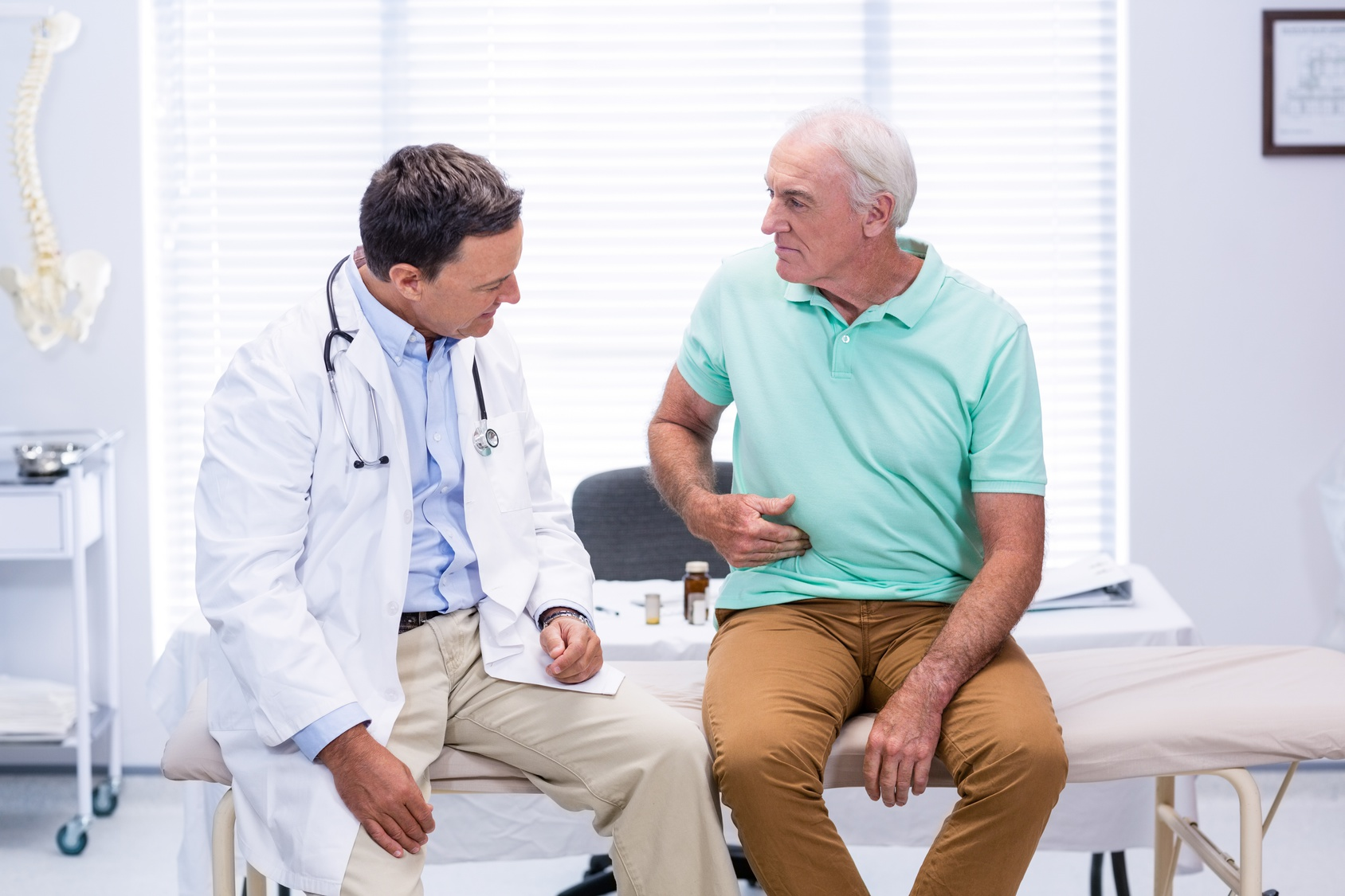 Médico e homem idoso sentados em maca conversando | Como se recuperar de uma endoscopia