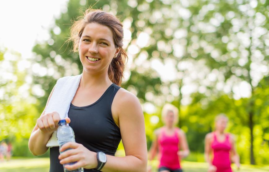 Mulher sorrindo com garrafa de água nas mãos | Complicações da Hepatite A
