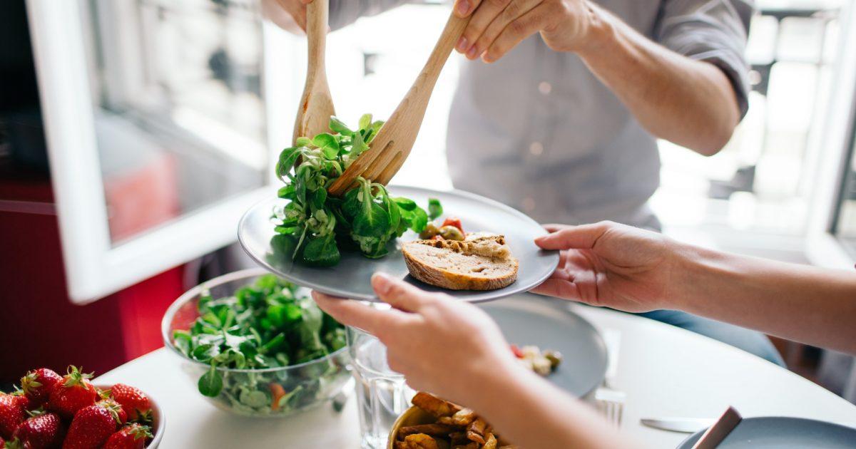 Pessoa servindo salada em um prato | Alimentos ricos em nutrientes para melhorar sua dieta