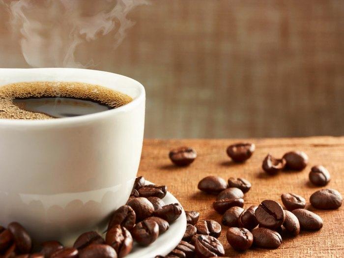 Xícara com café quente e grãos de café na mesa | Efeitos do café na digestão