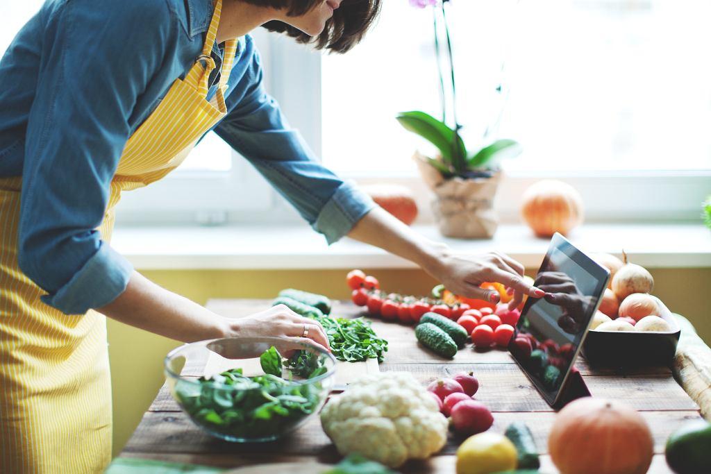 Mulher pesquisando no tablet e preparando salada | Mitos e verdades sobre alimentação