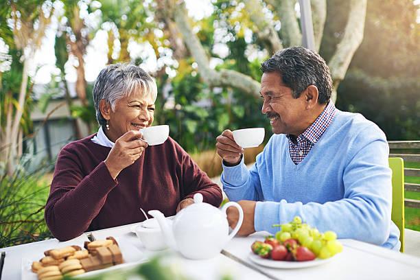 Casal de idosos tomando café ao ar livre | Hábitos para melhorar a digestão