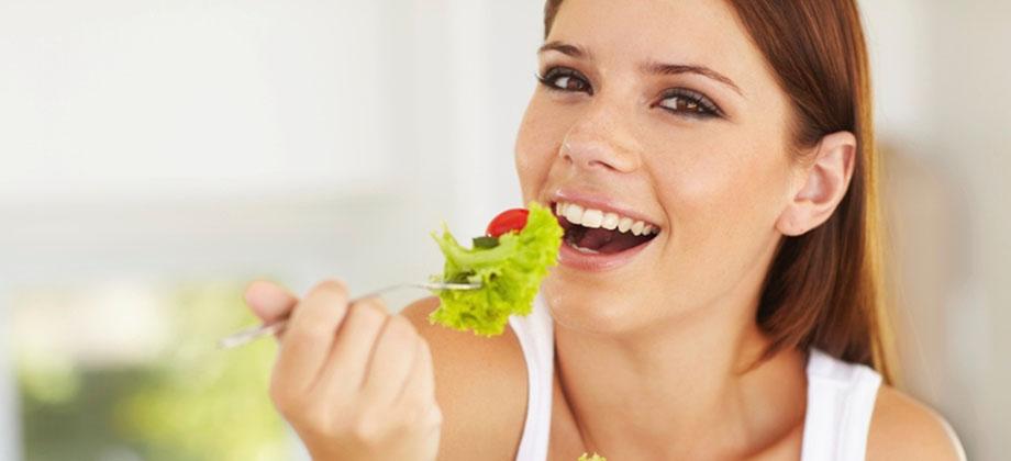 Como a mastigação pode influenciar no emagrecimento - Mulher colocando alface na boca | Instituto Digestivo