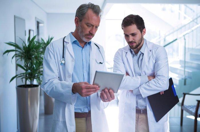 doutores conversando em corredor com tablet na mão | Diferença entre urologista e proctologista