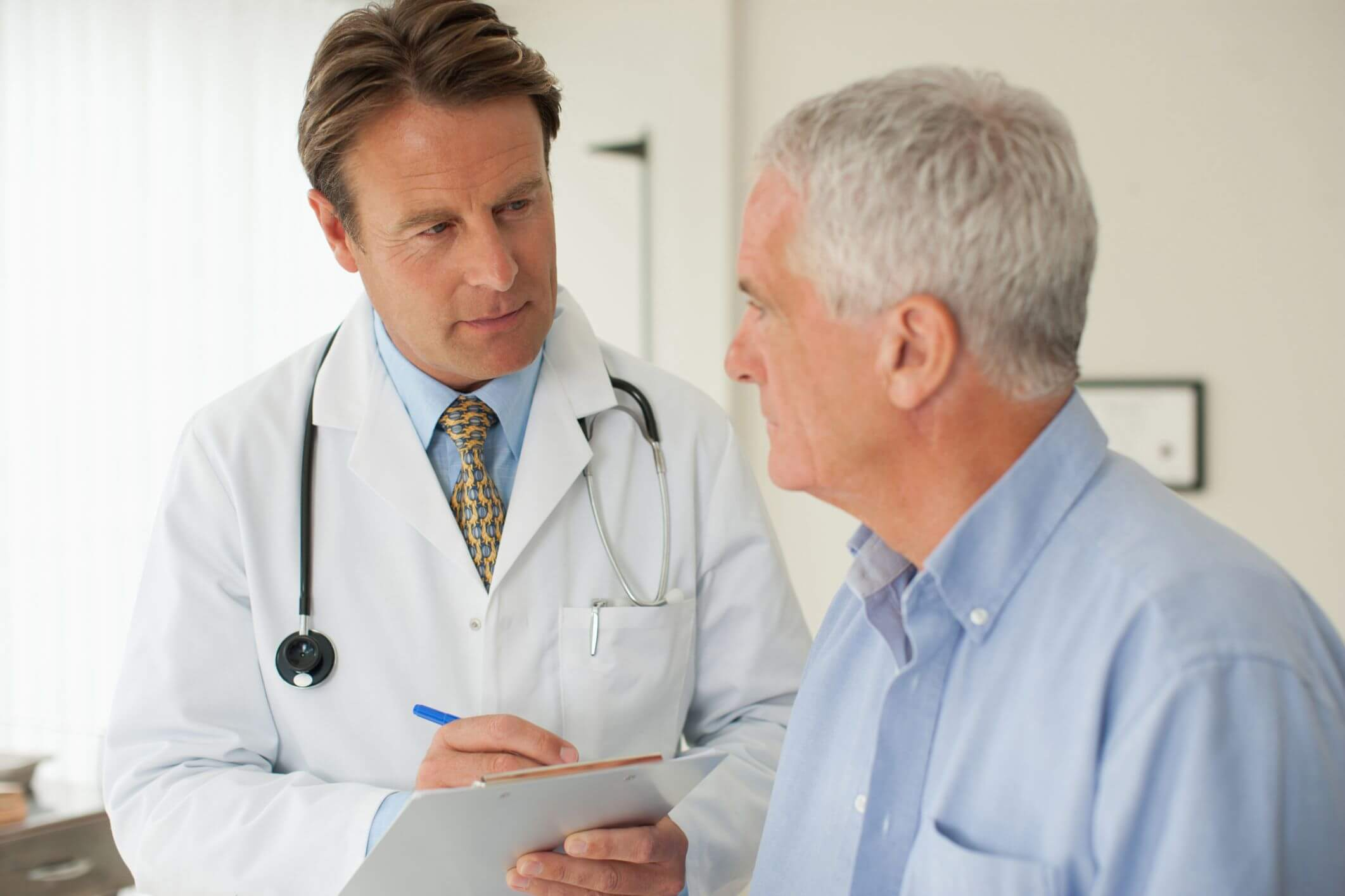 foto de doutor proctologista conversando com paciente idoso | Exames de proctologia: prevenção além do Novembro Azul