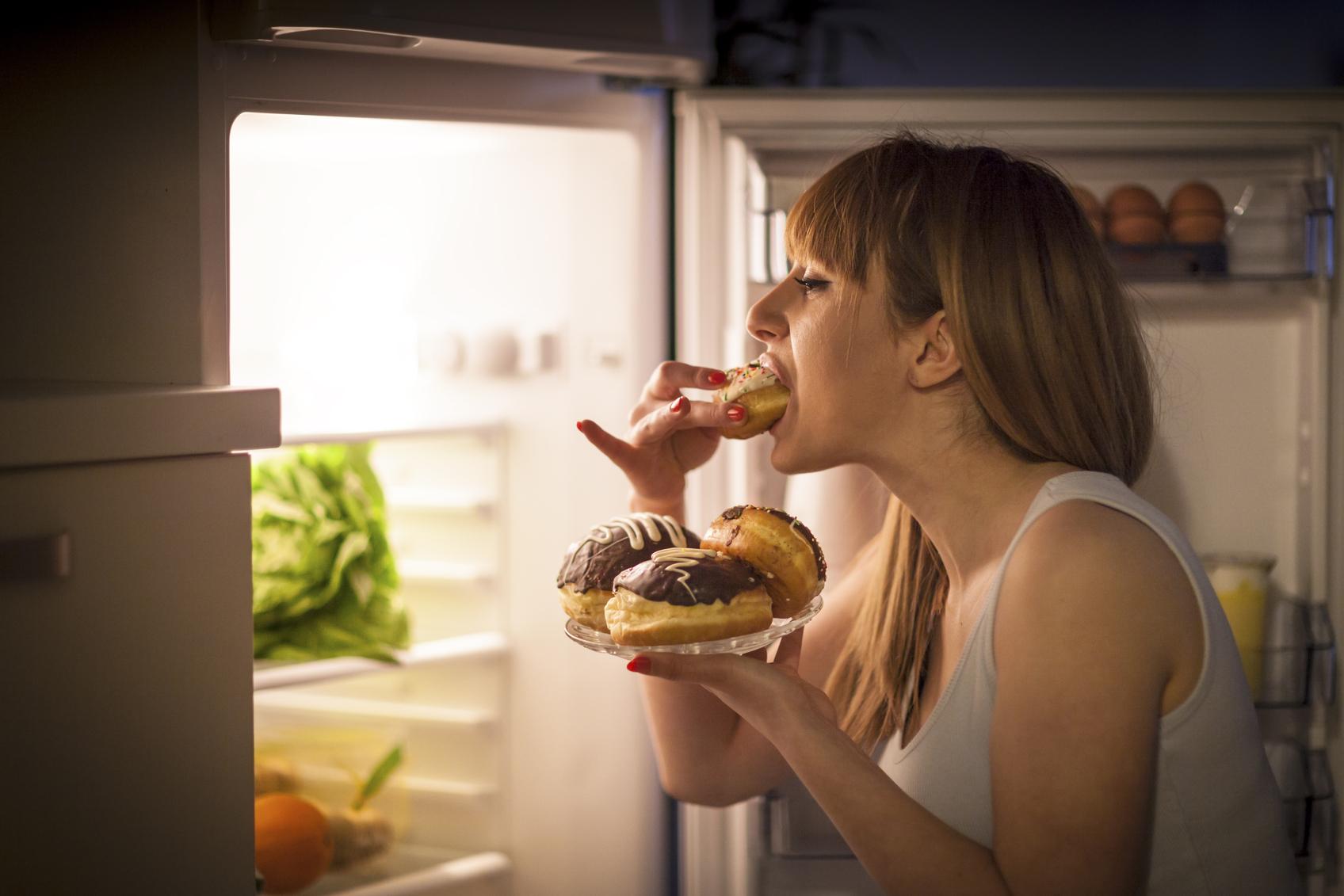 foto de mulher comendo doce antes dormir | Por que devemos evitar comidas pesadas antes de dormir?