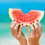 foto de mulher segurando melancia na praia | Alimentação no verão: como desfrutar a estação de forma saudável