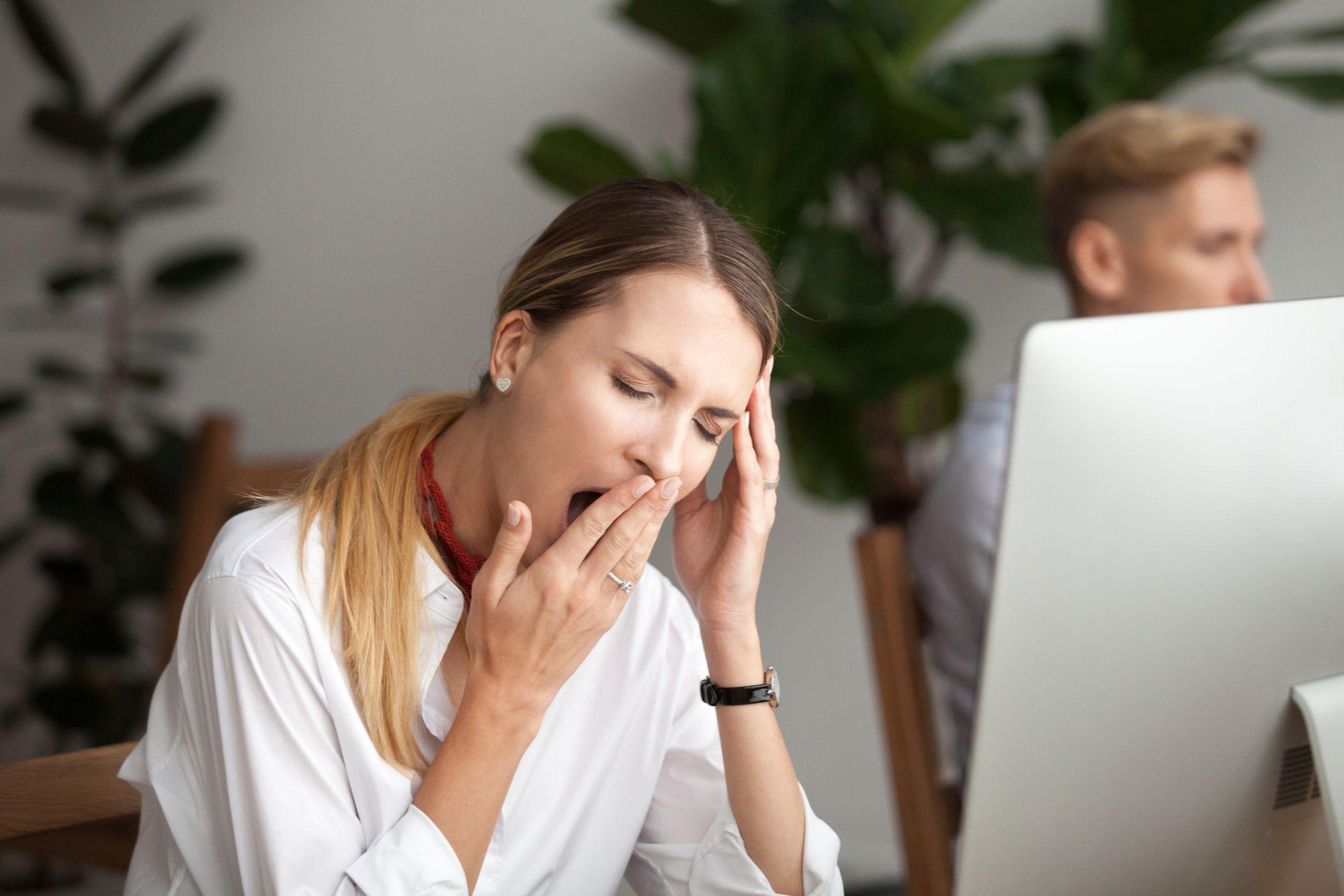 imagem de mulher bocejando no trabalho | Fadiga após o almoço? Descubra como despertar desse hábito!